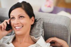 Mulher feliz que coloca no sofá e no móbil de fala imagem de stock royalty free