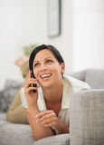 Mulher feliz que coloca no sofá e no telefone de fala fotografia de stock