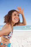 Jovem mulher feliz que coloca sua mão em sua testa para olhar distante a Imagens de Stock Royalty Free
