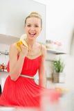 Jovem mulher feliz que come a banana na cozinha Fotografia de Stock