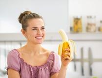 Jovem mulher feliz que come a banana na cozinha Imagens de Stock