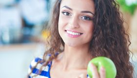 Jovem mulher feliz que come maçãs na cozinha Foto de Stock Royalty Free