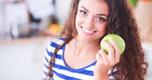 Jovem mulher feliz que come maçãs na cozinha Fotos de Stock Royalty Free
