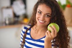 Jovem mulher feliz que come maçãs na cozinha Imagens de Stock