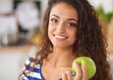 Jovem mulher feliz que come maçãs na cozinha Fotografia de Stock