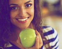 Jovem mulher feliz que come maçãs na cozinha Fotografia de Stock Royalty Free