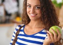 Jovem mulher feliz que come maçãs na cozinha Foto de Stock