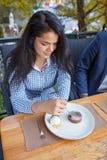 Jovem mulher feliz que come o bolo no café do ar livre imagem de stock royalty free
