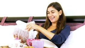 Jovem mulher feliz que come o café da manhã na cama vídeos de arquivo
