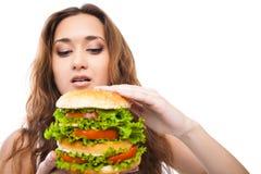 Jovem mulher feliz que come o hamburguer saboroso grande isolado Foto de Stock