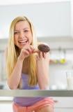 Jovem mulher feliz que come o queque do chocolate Fotografia de Stock Royalty Free