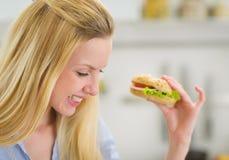 Jovem mulher feliz que come o sanduíche na cozinha Foto de Stock