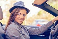 Jovem mulher feliz que conduz o convertible no dia ensolarado fotografia de stock