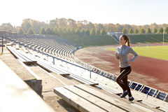 Jovem mulher feliz que corre em cima no estádio Imagem de Stock Royalty Free