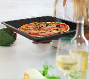 Jovem mulher feliz que cozinha a pizza em casa Fotografia de Stock Royalty Free