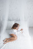 Jovem mulher feliz que encontra-se na cama imagem de stock