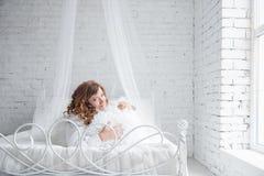 Jovem mulher feliz que encontra-se na cama imagens de stock