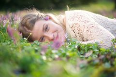 Jovem mulher feliz que encontra-se na grama e nas flores Imagens de Stock