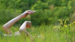 A jovem mulher feliz que encontra-se no gramado verde usa o smartphone no campo cênico no fundo do por do sol filme