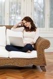 Jovem mulher feliz que encontra-se no sofá com portátil Fotografia de Stock Royalty Free
