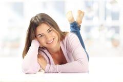 Jovem mulher feliz que encontra-se para baixo no assoalho Fotografia de Stock Royalty Free