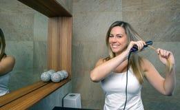 Jovem mulher feliz que endireita o cabelo com a imagem de stock