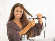 Jovem mulher feliz que endireita o cabelo com straightener Fotografia de Stock Royalty Free