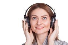 Jovem mulher feliz que escuta a música através dos fones de ouvido Foto de Stock