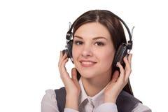 Jovem mulher feliz que escuta a música através dos fones de ouvido Imagem de Stock Royalty Free