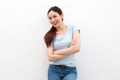 Jovem mulher feliz que está com os braços cruzados imagens de stock