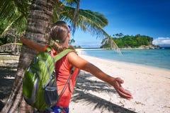 Jovem mulher feliz que está com a trouxa no mar e no lookin da costa Fotos de Stock Royalty Free