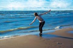 Jovem mulher feliz que está na praia foto de stock