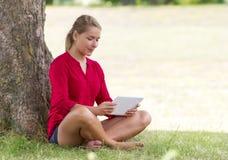 Jovem mulher feliz que estuda na tabuleta sem fio que senta-se na grama Foto de Stock