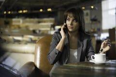 Jovem mulher feliz que fala no telefone em uma cafetaria Fotos de Stock Royalty Free