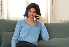 Jovem mulher feliz que fala no telefone esperto que senta-se no sof? em casa No lazer e na tecnologia fotos de stock