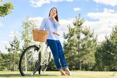 Jovem mulher feliz que fala no telefone no gramado verde foto de stock