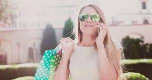 Jovem mulher feliz que fala sobre o telefone video estoque