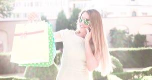 Jovem mulher feliz que fala sobre o telefone ao andar com os sacos de compras video estoque