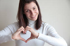 Jovem mulher feliz que faz a forma do coração com mãos Fotografia de Stock