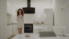 Jovem mulher feliz que faz o café na cozinha Senhora de sorriso que recebe a mensagem filme