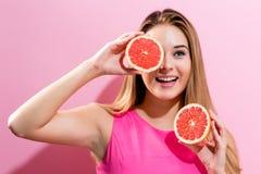 Jovem mulher feliz que guarda metades da toranja Foto de Stock