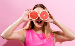 Jovem mulher feliz que guarda metades da toranja Fotografia de Stock Royalty Free