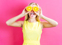 Jovem mulher feliz que guarda metades das laranjas Foto de Stock