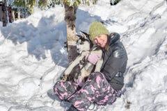 Jovem mulher feliz que guarda o cachorrinho ronco na neve Foto de Stock Royalty Free