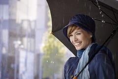 Jovem mulher feliz que guarda o guarda-chuva na chuva Foto de Stock Royalty Free