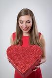Jovem mulher feliz que guarda um dia de Valentim grande do presente do coração Imagem de Stock Royalty Free