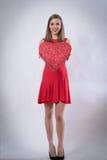 Jovem mulher feliz que guarda um dia de Valentim grande do presente do coração Foto de Stock Royalty Free