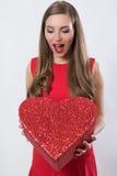 Jovem mulher feliz que guarda um dia de Valentim grande do presente do coração Imagem de Stock