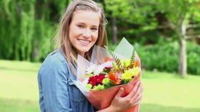 Jovem mulher feliz que guarda um grupo de flores vídeos de arquivo