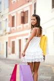 Jovem mulher feliz que guardara sacos de compras Foto de Stock